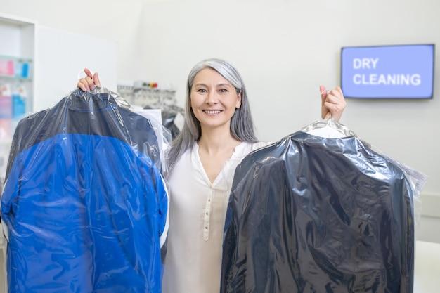 Счастливая красивая женщина улыбается, стоя в химчистке, показывая костюмы, упакованные в ящики