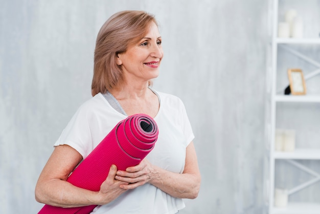Happy pretty woman standing in home holding roll of yoga mat in hand