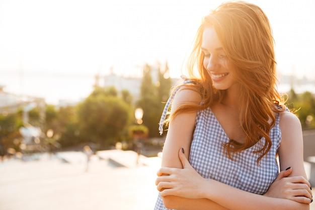 Счастливая милая женщина стоя с сложенными оружиями и смеяться над