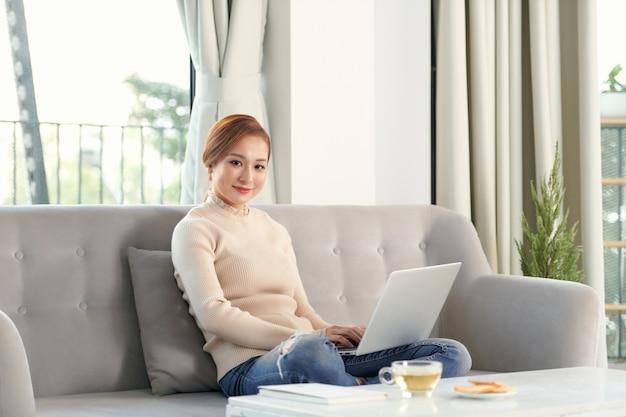 居心地の良いソファに座ってラップトップを使用して幸せなきれいな女性