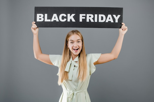 Happy pretty woman with black friday sign isolated over grey