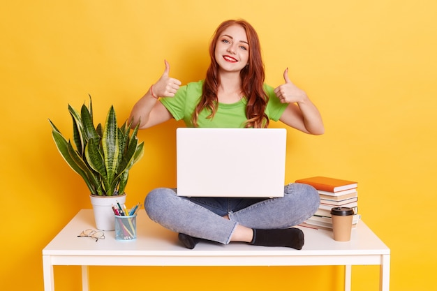 Happy pretty woman working with computer while sitting on white desk with crossed legs, lady wearing casual attire, showing thumbs up, being glad of finishing project.