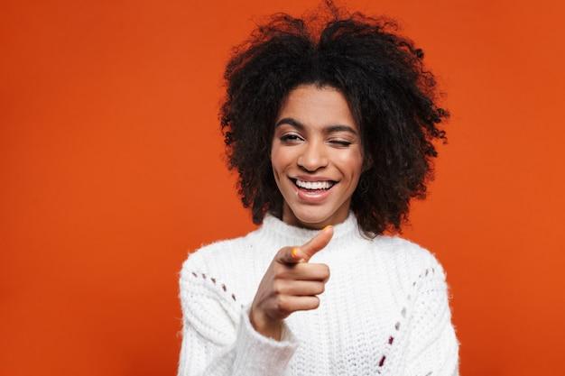 Счастливая довольно молодая африканская женщина указывая пальцем на переднюю изолированную над красной стеной, подмигивая