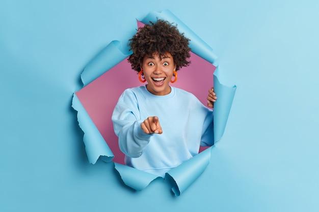 幸せなかなり若いアフリカ系アメリカ人の女性が人差し指であなたを指差す前に何か面白いものが長袖のジャンパーを着て紙の壁を突破するのを見る
