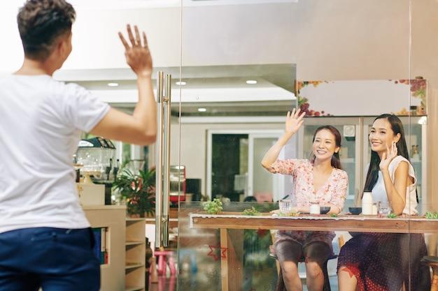 幸せなかなり若いアジアの女性の友人がカフェで朝食をとり、彼らの友人に手を振って