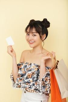 ショッピングバッグとクレジットカードを保持している幸せなかなり若いアジアの女性