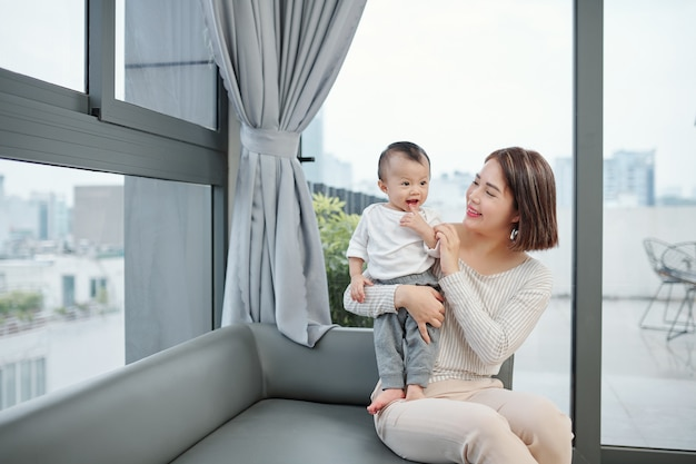 Happy pretty young asian woman looking at little daughter standing on her laps