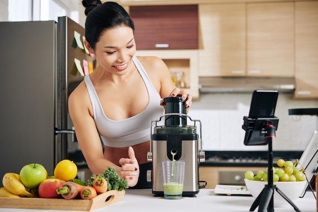아침 식사로 과일과 야채 주스를 만드는 자신을 녹음하는 행복한 예쁜 아시아 여성