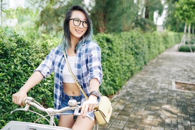 Счастливая довольно молодая китаянка в очках, езда на велосипеде в городском парке