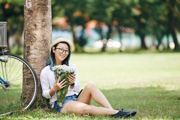 Happy pretty young chinese woman sitting under tree in park and loonig at bouquet of daisies in her hands