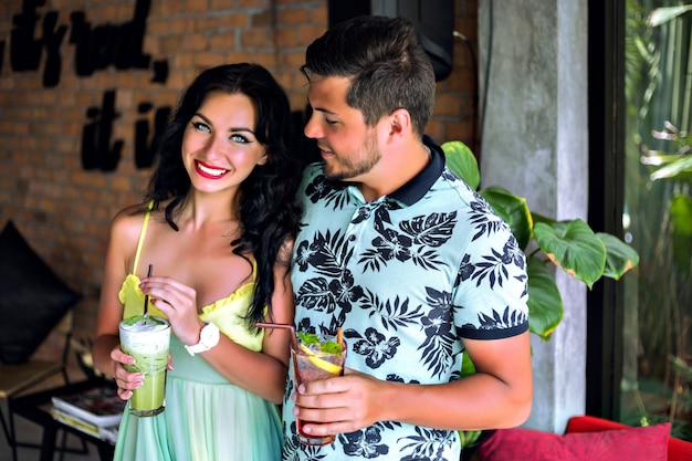 Happy pretty young couple enjoying their tasty sweet cocktail at tropical bar, color matching trendy clothes, summer vacation mood. perfect romantic date.