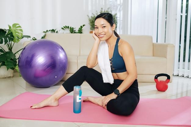 Счастливая довольно молодая азиатская женщина с полотенцем на плече, отдыхая на коврике для йоги после тренировки дома