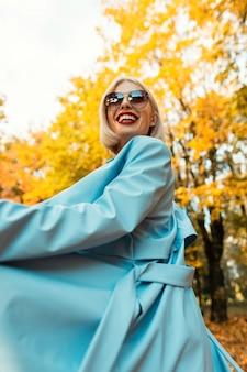 青いコートのヴィンテージサングラスと幸せなかなり若い笑顔の女性は明るい秋の黄色の葉と秋の公園を歩きます