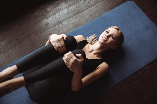 Happy pretty young sportswoman lying and stretching