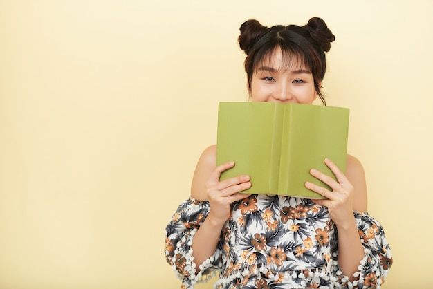 Happy pretty young vietnamese woman hiding her smile behind opened book and looking at camera