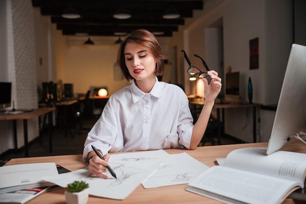 幸せなかなり若い女性のファッションデザイナーが座って、オフィスでスケッチを描いています