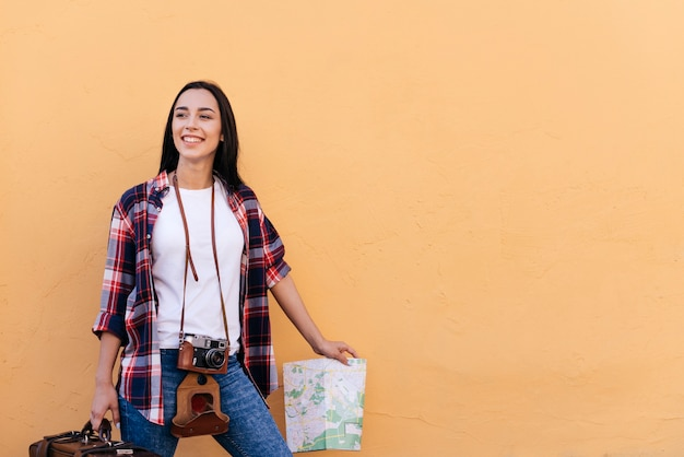 Happy pretty young woman holding bag and map standing near peach wall