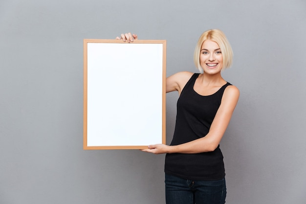 Happy pretty young woman holding blank white board over gray wall