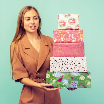 Happy pretty young woman holding gift box over blue background. chrismas and new year concept