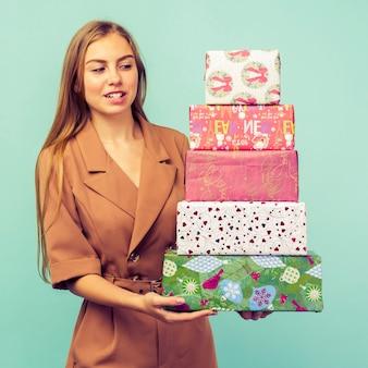 青い背景の上にギフトボックスを保持している幸せなかなり若い女性。クリスマスと新年のコンセプト