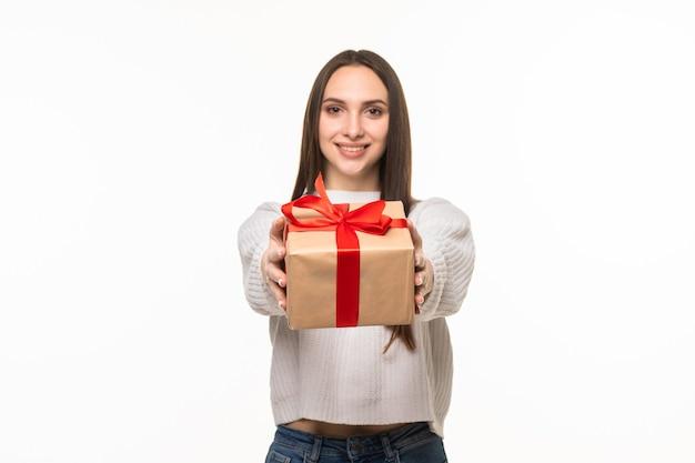Счастливая симпатичная молодая женщина, держащая подарочную коробку над серой стеной
