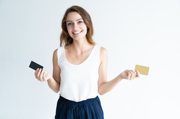 Happy pretty young woman holding two plastic cards
