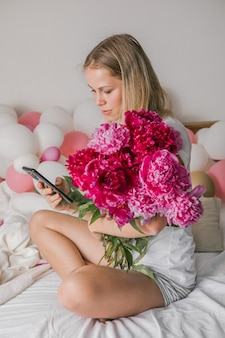 Happy pretty young woman at home  in bedroom in bed holding flowers take a selfie by mobile phone
