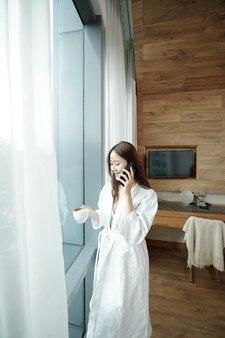 목욕 가운을 입은 행복한 젊은 여성이 침실 창가에 서서 커피를 마시고 남자 친구와 전화 통화를 합니다.