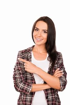 Счастливый красивая молодая женщина в клетчатой рубашке, указывая в сторону