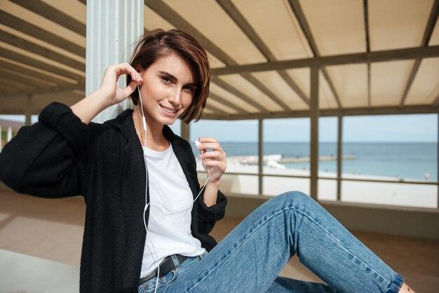 앉아서 해변 테라스에서 음악을 듣고 이어폰에 행복 꽤 젊은 여자