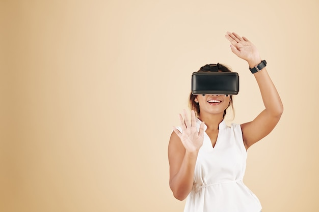 ビデオゲームをプレイし、彼女の前の見えない壁に触れるvrヘルメットの幸せなかなり若い女性