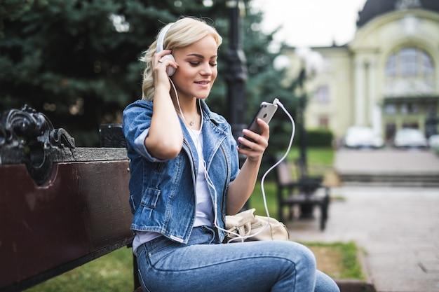 Счастливая красивая молодая женщина, слушающая музыку в наушниках и использующая смартфон, сидя на скамейке в городе