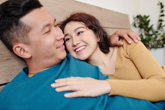 Happy pretty young woman lying on bed with boyfriend and looking at him with love and tender