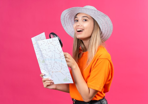A happy pretty young woman in an orange t-shirt wearing sunhat holding a map with magnifying glass while looking side on a pink wall
