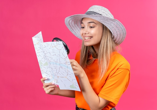 A happy pretty young woman in an orange t-shirt wearing sunhat looking at a map with magnifying glass on a pink wall
