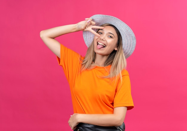 A happy pretty young woman in an orange t-shirt wearing sunhat showing her tongue with two hands gesture while looking on a pink wall