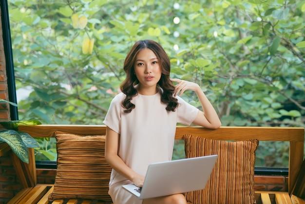 Счастливая довольно молодая женщина, сидящая на диване и использующая ноутбук дома