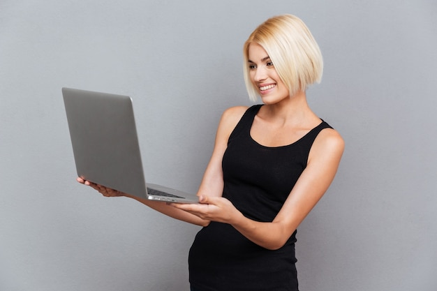 Happy pretty young woman smiling and using laptop over gray wall