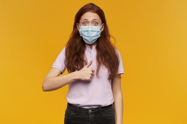 立っている黄色の壁の上に医療保護マスクを身に着けて、黄色の壁の上に分離されたジェスチャーを示す幸せなかなり若い女性