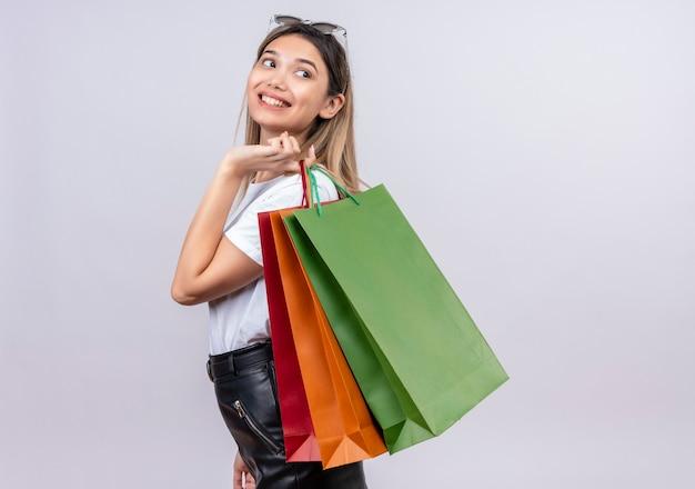 Una donna abbastanza giovane felice in occhiali da sole da portare della maglietta bianca sulla sua testa che tiene i sacchetti della spesa su una parete bianca