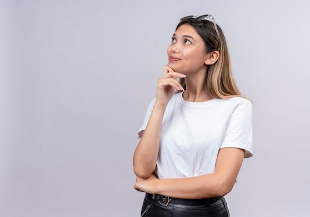 Una bella giovane donna felice in maglietta bianca che indossa occhiali da sole sulla sua testa tenendo la mano sul mento mentre pensa su un muro bianco
