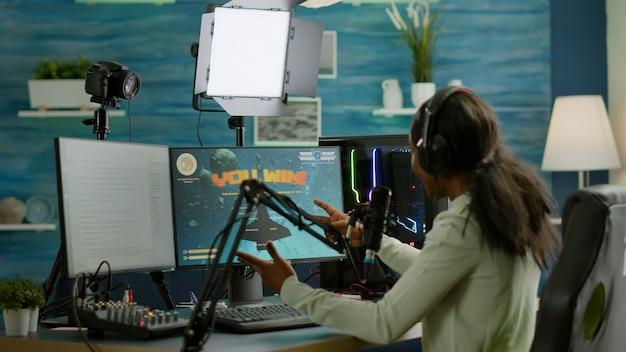 비디오 게임에서 우승한 후 경쟁하는 동안 행복한 전문 아프리카 전자 스포츠 선수. 네온 불빛으로 집에서 비디오 게임 토너먼트 동안 온라인 스트리밍 사이버 공연.