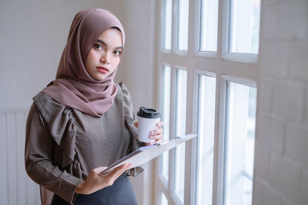 Happy professional arab businesswoman brown hijab working at home.