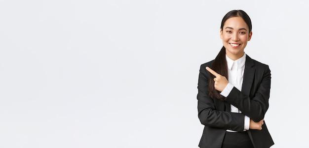 Счастливый профессиональный азиатский женский менеджер, бизнесвумен в костюме, показывая объявление, улыбаясь и указывая пальцем влево на баннер продукта или проекта, стоя на белом фоне