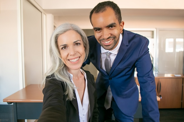 Happy professional partners posing for photo, smiling and looking at camera. african american successful businessman and caucasian businesswoman taking selfie. teamwork and business concept