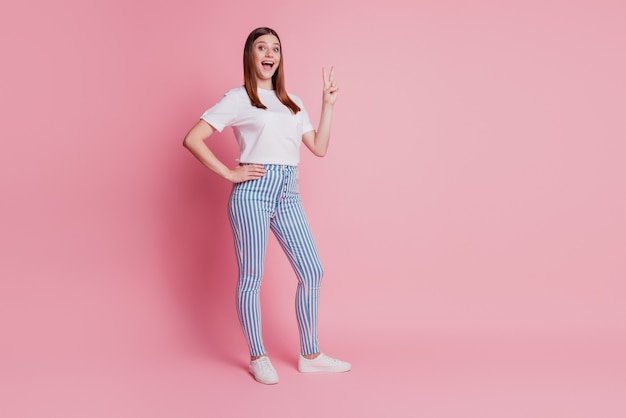 Happy promoter young person showing way with fingers indicate empty space on pink background
