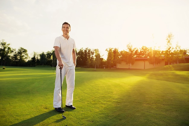 Happy proud golf player holding a club on a lawn.