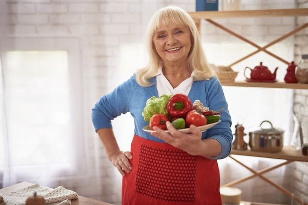 Happy proud old lady at kitchen holds vegetables.