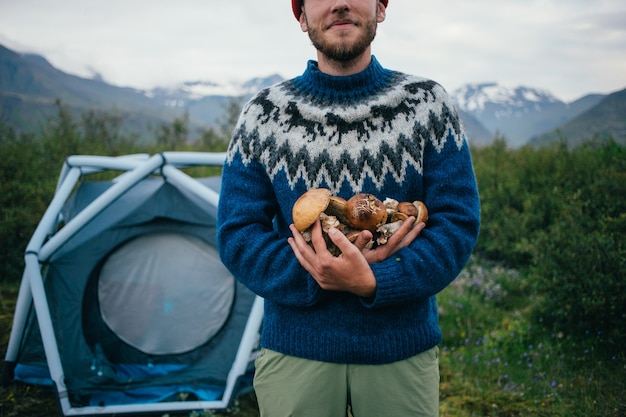 Happy, proud picker man in traditional blue wool sweater with ornaments stands on camping ground in mountains, holds in arms pile of delicious and organic mushrooms