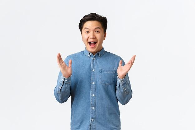 Felice, orgoglioso e compiaciuto, maschio asiatico, applaude le mani. ragazzo allegro sorpreso che applaude e si congratula con il successo, lodando l'ottimo lavoro, dicendo ben fatto al collega, sfondo bianco.